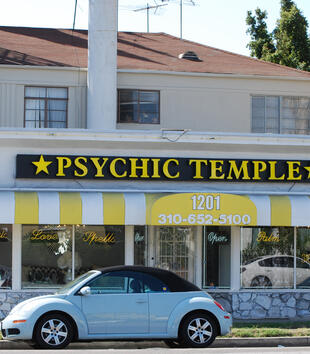 "A white, rectangular building has a striped yellow and white awning and a black sign that reads, ""PSYCHIC TEMPLE."" Two gold stars frame the sign. The neon signs in the window read, ""Love,"" ""Spells,"" ""Palm,"" and ""Tarot."""