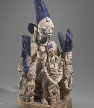 A wooden figurine depicts a woman mounted on horeseback while holding a fan and rooster. She has a cool, expressionless face and large blank eyes. Smaller figures gather around her and one joins her on the animal. The group is painted white and blue.