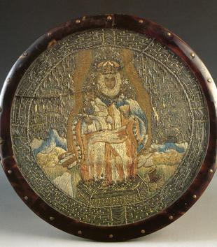 A circular tortoiseshell frame holds an embroidered image of an enthroned Virgin wearing a light blue cloak and holding the Christ child. Both wear royal coronets. A treasure chest lies open on the ground at their feet.