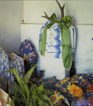 An altar includes plants, an antler that has been hung with a cloth parcel and bow, and floral patterned cloths.