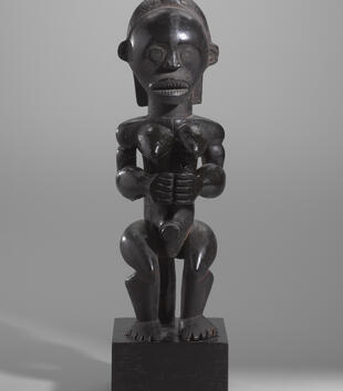 A wooden female figure carved of wood and highly polished has a muscular body and a bold gaze. She has a mouth full of pointed teeth, small eyes, and pointed breasts. She clasps her hands at her waist.