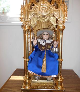 A light-skinned figure of a young boy wears a shiny blue robe, brown stole, and wide-brimmed hat. He is seated in a gold throne with an ornate canopy carved with a lamb insignia. The child holds a basket and staff.