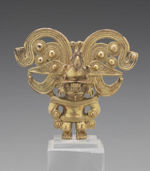A golden finial depicts a squat, stylized male figure wearing an ornate headdress. The headdress is composed of a cast, beaked bird placed against a pair of stylized animal heads in profile and decorative spirals that rise behind it.