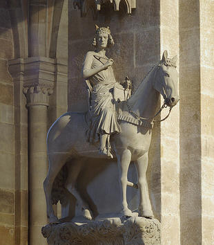 A leafy, carved pedestal on a stone pillar holds a pale stone sculpture of a horse with a regal rider. The rider wears a crown and draping robes and cloak. A sculpture of castle in miniature is affixed to the wall above the group.