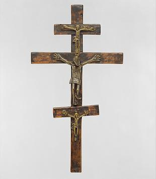 A wooden object consists of three crucifixes stacked vertically. A cast metal, Christ figure is affixed to each crucifix. Their hands are outstretched, their waists covered with loin cloths, and their ribs visible.