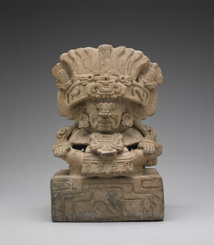 An urn is shaped like a deity sitting cross-legged and wearing a feathered headdress. Corncobs sprout from the headdress whose band is carved with S-shapes. The deity has earrings and a nose ornament, and he sits a rectangular box.