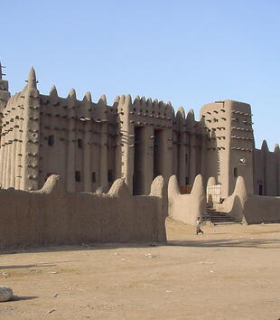 The smooth exterior of an adobe mosque is decorated with sticks of palm that jut out all over its surface. The mosque has a large trapezoidal shape with high walls that are topped by a series of cone-shaped protrusions.