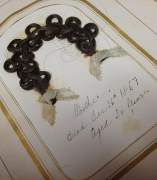 "A gold border encircles a braided piece of hair arranged in an arc on a book page. Bows are tied on the hair tips. Handwritten script below reads, ""Mother. Died Dec. 16th 1867. Aged 56 years."""