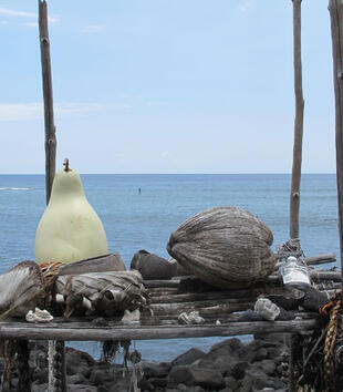 An altar has been constructed on a rocky ocean shore. It consists of a wooden platform between four poles with offerrings of gourds, a coconut, and a bottle of alcohol.