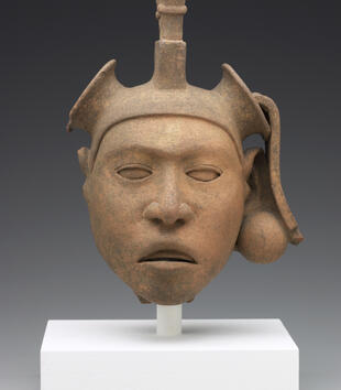 The face of a ceramic head has almond-shaped eyes, a small nose, and slightly parted lips. Only remnants of his headdress remain, and it is decorated with a line of vertical stalks.
