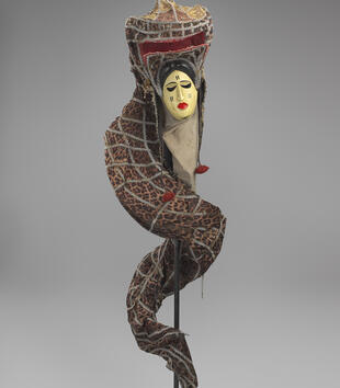 A masklike face with a red lips and black eyes hangs from a large leopard print headdress with swirling train of textile decorated with metallic thread.