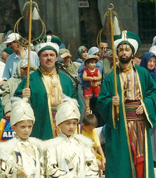 A procession includes three figures in green robes and caps holding gold staffs hung with crescent moons. Two children in white uniforms also march.