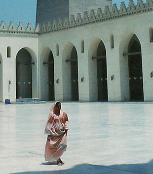 A photo captures a woman walking through the open courtyard of a mosque. The rectangular courtyard consists arcades on all four sides.