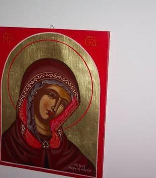 A painting of a light-skinned Mary with a large, oblong disk of gold leaf light behind her head is painted on a red background. She has large stylized eyes, red lips, and wears a burgundy cloak.