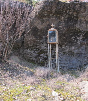A small rusted houselike shrine stands on a four-legged podium against a rock face.