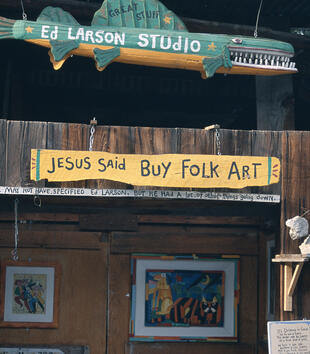 """Hung on the lintl of wooden, shop stall is a sign painted with the words, """"Jesus said buy folk art."""" A smaller sign beneath reads, """"He may not have specified Ed Larson. But he had a lot of other things doing down."""""""