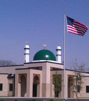A flat-roofed, tan mosque has simple, square windows and pointed archways. A green dome with white minarets tops the building. An American flag stands in front of the complex.