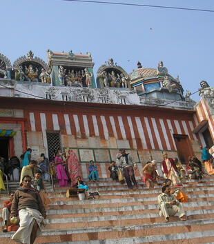 People gather on the steps of a red and white striped temple with straight walls. It is topped with a series of colorful niches that hold figural sculptures. A multi-colored dome is visible in the background.