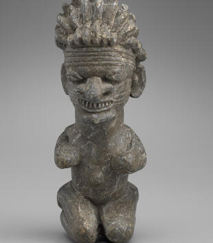 A soapstone sculpture depicts a nude kneeling woman with an oversized head, robust facial features, and a mass of rippling hair. She is carved with a mouth full of teeth and a bulbous nose, and lines are incised around her forehead.