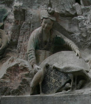 A woman sculpted of gray stone emerges from a rocky outcropping. She reaches her arms out over a sculpted basket with two thin birds in front of it and small chicks underneath it.