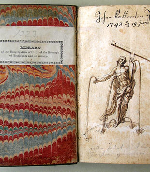 A small book lies open to expose a marbled interior cover which faces an illustrated page. This page depicts a muscular Christ in flowing drapery. He grasps a t-shaped cross in his left hand. Blood flows in long spurts from his hands, feet, and side.