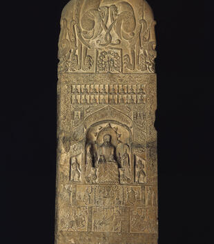 A pale stone slab is covered with low relief carvings. A central niche holds an ethroned figure carved in higher relief among his attendants. A variety of figures and processional scenes surround him as well as abstract vining and floral motifs.