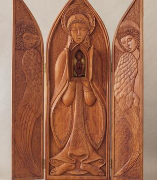 A willowy figure of Mary is carved on the center panel of a wooden folding triptych. She has niche located behind small doors carved in her chest. It holds a carved sculpture of a haloed child. Angels are depicted on the side panels.