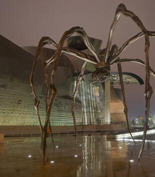A monumental steel spider has eight slender, misshapen, and curving legs. The spider's body is suspended high in the air, and an egg sac is visible beneath the body. The sculpture is photographed beside a modern building at nighttime.