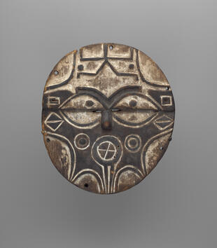A dark wooden, oval mask is incised and painted with a geometric face. It has white, almond eyes, a circular mouth, and other geometric motifs in white that decorate the cheeks and foreheads.