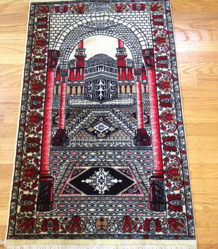 A prayer rug depicts the black, square Kaaba woven in an ornate red, white, and black architectural space. The setting includes columns, arcades, and patterned rugs.