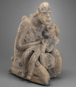 A terracotta figurine depicts a kneeling figure tenderly holding a child across her lap. She has an oval head with simple facial features, including protruding lips and eyes. One of her hands holds the child's head close as he opens his mouth in a cry.