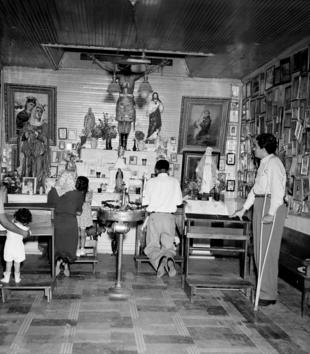 A black and white photo shows a space with adults and children on kneelers before an altar arrayed with devotional statues. The walls are lined with small framed images. One devotee stands on crutches.
