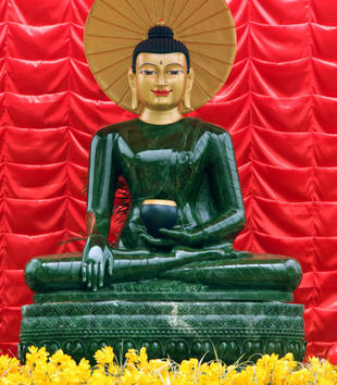 A large, shiny jade figure sits cross-legged on a carved platform. The head is gold with large eyes, long earlobes, a black topknot, and serene expression. It holds a small black object. The figure sits against a red background and among yellow flowers.