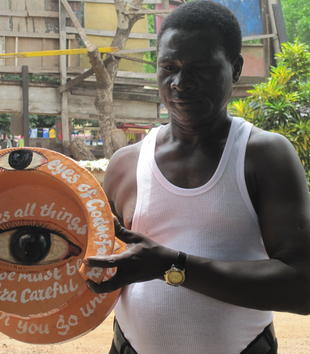 A dark-skinned man wearing a white t-shirt holds a large, broken mortar transformed into an art object. It is painted orange with a large eye depicted at center. Other smaller eyes cover the object's surface. Neat, white text also covers the piece.
