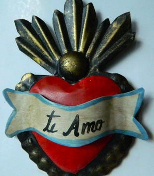 "A small red metal heart is fashioned with a white and blue banner unfurled across it. The banner is inscribed with ""te Amo"" in black, handwritten script. Abstract, metal flames emerge from the top of the heart."