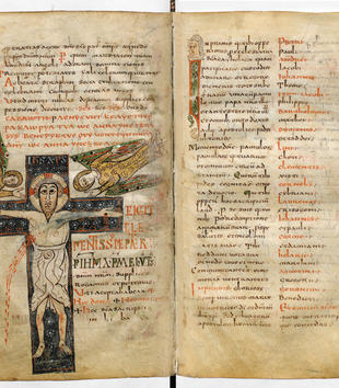 A manuscript page with black and red text depicts Christ on a blue, floral cross. A pale, blood-spurting Christ is nailed to the cross. The geometric figure has large open eyes but stiff limbs and drapery. Two angels swoop around the crucifix.