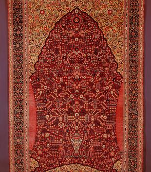 An ornate red rug is woven all over with small, geometric floral motifs. A red mass of flowers emerges from a small white vase represented within a gateway shape.