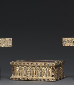 A gem-encrusted gold altar is a squat rectangular box with a white-speckled porphyry top and ornately carved sides. It is shown between two gold, gem-covered crosses.