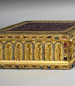 A gem-encrusted gold altar is a squat rectangular box with a white-speckled porphyry top. Archangels, apostles, and Christ are shown within a colonnade depicted on the object's sides.
