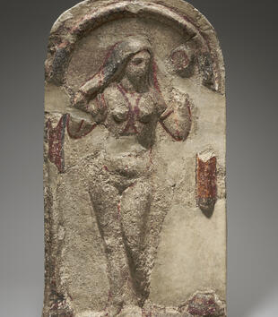 A nude female figure emerges in low-relief from a curved limestone niche. Much of the stone and paint has worn away from the work, so her arms and waist are missing. Some red lines criss-cross her chest and outline her arms.