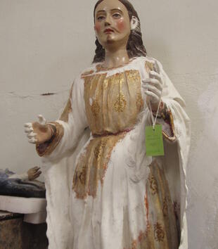 A wooden polychromy sculpture depicts a light-skinned figure with long brown hair, rosy cheeks, and painted red lips. He is carved with his arms outstretched and wearing draping golden robes. A lot of the paint has worn from the saint's dress and hands.