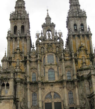The ornate facade of a cathedral includes a proliferation of large glazed windows, columns, undulating broken pediments, and sculpture. The building also includes two large bell towers that are equally as ornate with an explosion of finials and coumns. .
