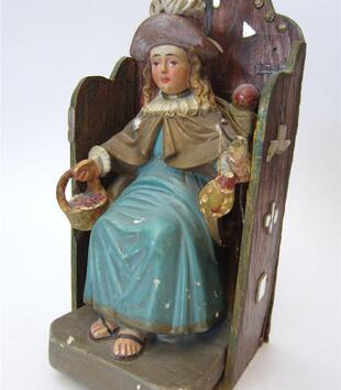 A painted, plaster figurine of a light-skinned child in a blue robe, tan cloak with a white collar, and brown hat is carved on a wooden throne. The child wears a stoic expression with large, placid brown eyes. He holds a basket of fruit.