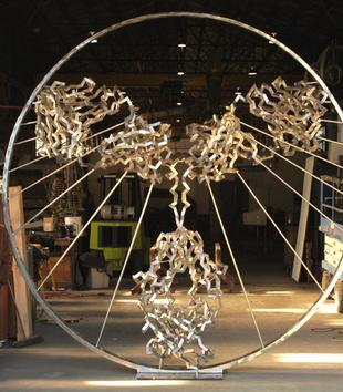 A sculpture stands in a garage space. It is formed by lines of jagged twisted metal that create abstract wings on a bodylike shape. Thin metal spokes emanate from the figure to connect it a large, encircling metal ring.