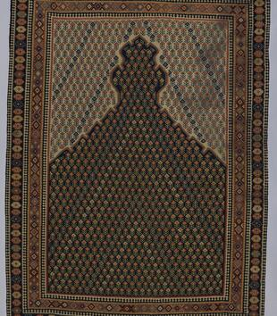 Woven in an earth-toned rug is an arched mihrab filled with a repeating pattern of geometric yellow, orange, and red flowers. An ornate border around the rug is woven with decorative geometric motifs.