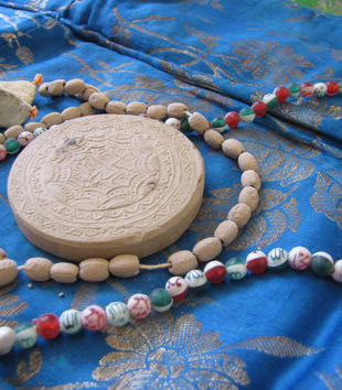 Devotional objects lie on a blue silken prayer rug. A circular, decoratively-carved piece of clay lies among two sets of prayer beads and two sachets.