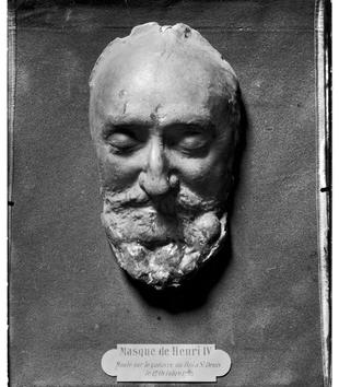 "A plaster cast captures the features of a bearded and mustached man with slightly sunken, closed eyes. A metal plaque at the bottom labels the cast, ""Masque de Henri IV."""