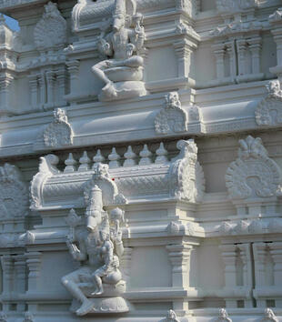 A white temple facade is ornately carved with crown motifs and sculpture. The figures depict the boar avatar of Vishnu. The many armed god has a boar's head on a human body and he sits on a lotus cushion. One of the figures has a small goddess on his lap.