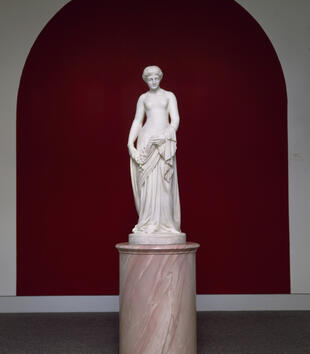 A pale white statue of a thin woman draped in a dress stands on a pink marble pedestal. The work is located against a red wall in a spare room.