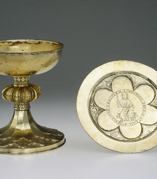 A silver-gilt chalice has a flat bowl on a stem engraved with trefoil leaves and decorated with a twelve-lobed knob. A paten beside it is engraved with Christ in Majesty in a hexafoil reserve and surrounded by spandrals engraved with the Evangelists.